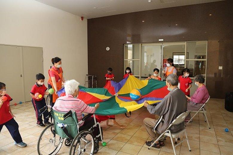 孩子與長者間合作無間,家園內充滿歡笑聲,不分老幼年紀,各個都露出滿足的笑容。(嘉義縣政府 提供)